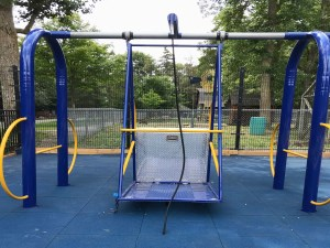 playground equipped with blue and yellow wheelchair swing with rubber matting underneath