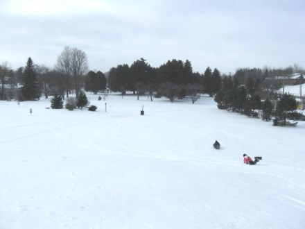 snowy toboggan hill at the disc golf park with a a toboggan rider