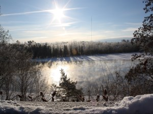 Sunshine and view of the river with trees covered in snow and ice