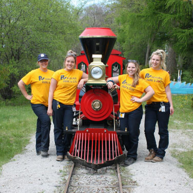 four employees posing with a mini train
